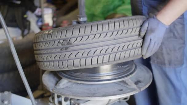 Szakképzett ember autószerelő teszi gumiabroncs az autógumi az autószerviz garázs.