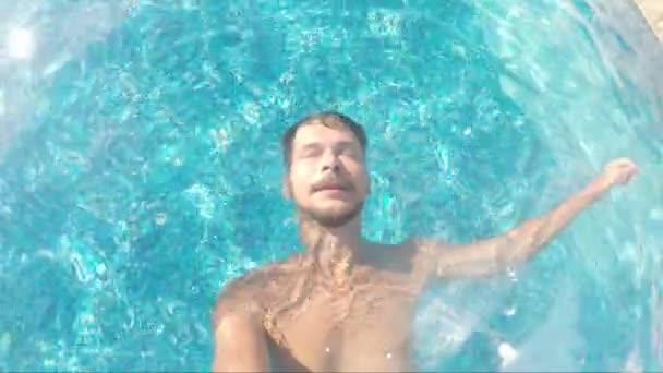 Dospělá vousatá brunetka se na zádech plaví v modré vodě v bazénu