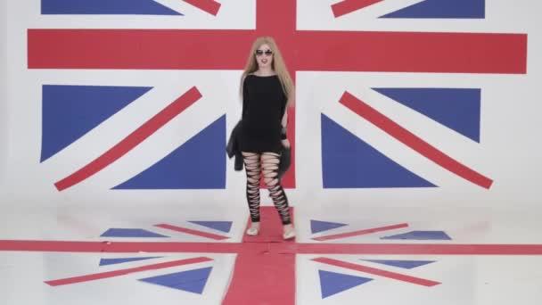 Hezká blondýnka se dívá na kameru, směje se a tancuje ve studiu s vlajkou Velké Británie.