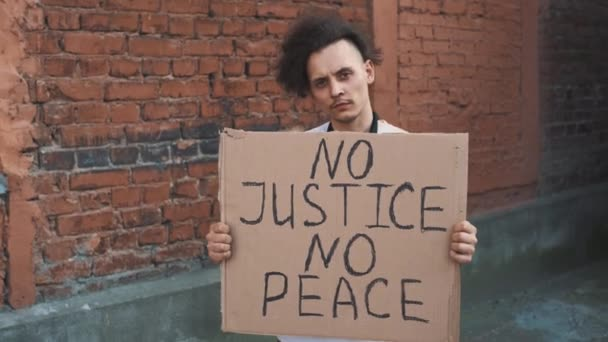 Caucasian man in mask stands against red wall with cardboard poster in hands with inscription - NO JUSTICE NO PEACE. Single protest.