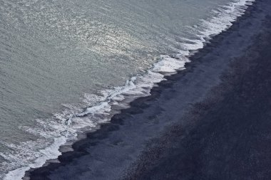 Waves of the Atlantic ocean fall on the black sand of the beach