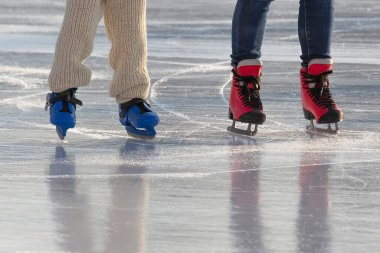 feet of different people skating on the ice rink. hobbies and leisure. winter sports