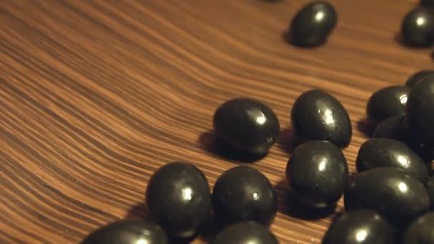 Černé olivy na hnědé dřevěné pozadí. 2 výstřely. Zpomalený pohyb. Úzká-up.1. olivy se valily (zleva doprava) na hnědé dřevěné background.2. Vodorovně (zleva doprava) pánev