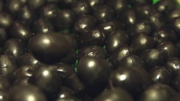 Černé olivy. 2 výstřely. Zpomalený pohyb. Úzká-up.1. černé olivy pádu dolů. Vertikální (zdola nahoru) pánev. 2. horizontální (zprava doleva) pánev