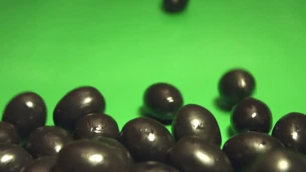 schwarze Oliven auf grünem Hintergrund. 2 Schüsse. Zeitlupe. Nahaufnahme. Oliven rollen auf grünem Grund herunter. horizontal (von rechts nach links) schwenken.