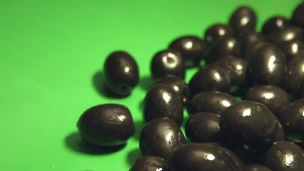 Černé olivy na zeleném pozadí. 2 výstřely. Zpomalený pohyb. Úzká-up.1. olivy se valily (zleva doprava) na zelený background.2. Horizontální (zprava doleva) pánev