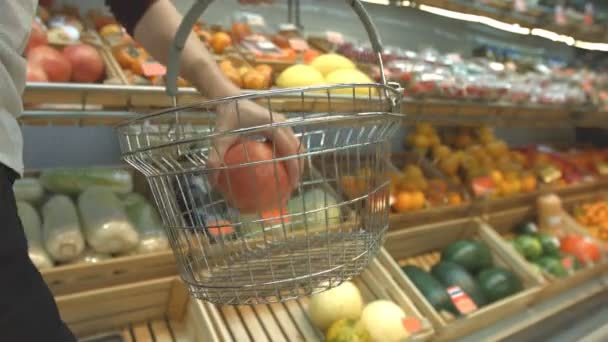 Fruit basket in the supermarket.Mens hands carry a grocery basket in the supermarket and put different fruits in it: pomegranate, melon, oranges, tangerines. On the shelfs are many other fruits and vegetables: persimmons, strawberries, watermelons,