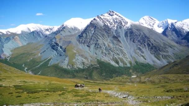 Hory se zasněženými vrcholky. Turisté jít cestou, v pozadí pohoří Altaj