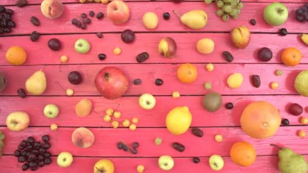 Gyümölcs rózsaszín ökológiai háttér. Felülnézet. Különböző gyümölcsök találhatók rózsaszín fa eco háttér. Férfi kezét coconat táblából veszi. Itt vannak: coconat, meggy, nektarin, alma, őszibarack, dátum gyümölcs, banán, citrom, körte, kókusz, szilva