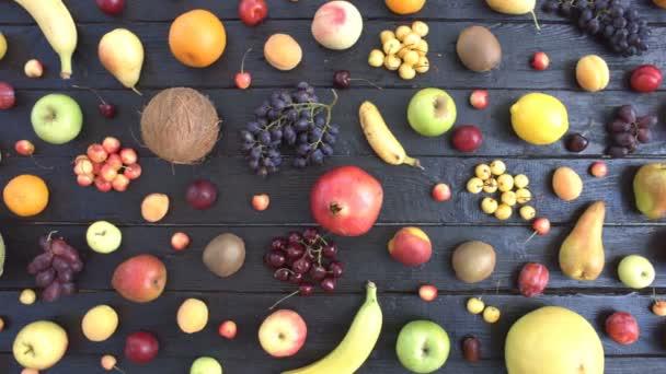 Gyümölcsök, fekete ökológiai háttér. Felülnézet. Különböző gyümölcsök találhatók, a háttér fekete fa eco. A táblázat eco: cseresznye, citrom, mandarin, őszibarack, körte, coconat, szőlő, kiwi, banán.