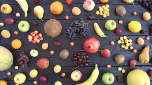 Ovoce na černém ekologické pozadí. Pohled shora. Různé druhy ovoce jsou umístěny na pozadí černé dřevěné eco. Ruce si meloun z eco tabulky. Zde jsou: banány, citron, třešně, pomeranče, mandarinky, broskve, hrušky