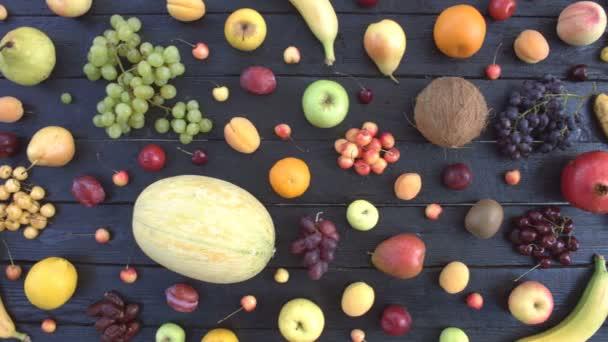 Gyümölcsök, fekete ökológiai háttér. Felülnézet. Különböző gyümölcsök találhatók, a háttér fekete fa eco. A táblázat eco: coconat, szőlő, narancs, banán, cseresznye, citrom, mandarin, őszibarack, körte.