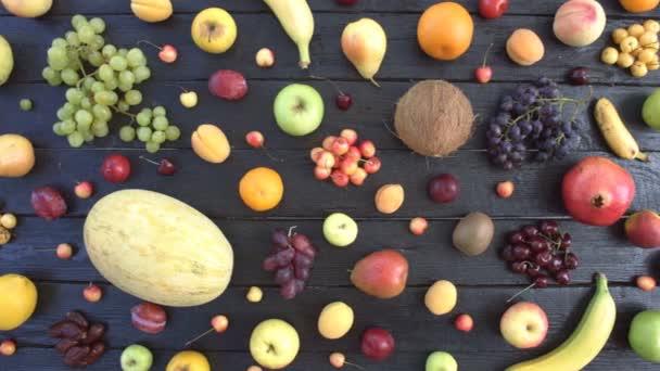 Ovoce na černém ekologické pozadí. Pohled shora. Různé druhy ovoce jsou umístěny na pozadí černé dřevěné eco. Pánská ruka klade žluté třešně na stůl eco. Zde jsou: granátová jablka, broskve, pomeranče, mandarinky, citron, hrušky, banány.