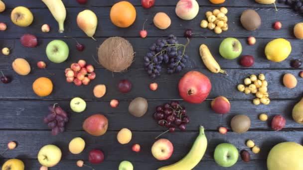 Ovoce na černém ekologické pozadí. Pohled shora. Různé druhy ovoce jsou umístěny na pozadí černé dřevěné eco. Pánská ruka klade hrozny na stůl eco. Zde jsou: švestky, kiwi, kokos, pomeranče, hrušky, banány, granátového jablka, broskve