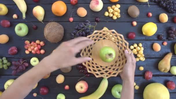 Gyümölcsök, fekete ökológiai háttér. Felülnézet. Különböző gyümölcsök találhatók, a háttér fekete fa eco. A férfi kéz elfoglalják gyümölcsök a fából készült lemez. Íme: alma, őszibarack, mandarin, szőlő, körte, banán, sárgadinnye, kókusz, szilva