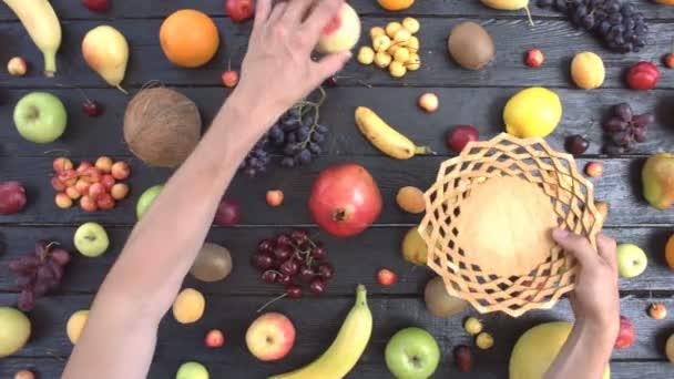 Ovoce na černém ekologické pozadí. Pohled shora. Různé druhy ovoce jsou umístěny na pozadí černé dřevěné eco. Ruce si ovoce na dřevěnou desku. Zde jsou: jablka, broskve, pomeranče, hrozny, hrušky, banány, meloun, kokos, švestky, granátové jablko