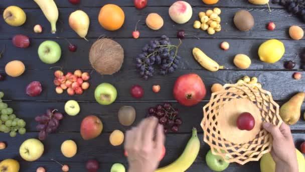 Ovoce na černém ekologické pozadí. Pohled shora. Různé druhy ovoce jsou umístěny na pozadí černé dřevěné eco. Ruce si ovoce na dřevěnou desku. Zde jsou: švestky, kiwi, hrozny, pomeranče, hrušky, banány, meloun, kokos, švestky, granátové jablko