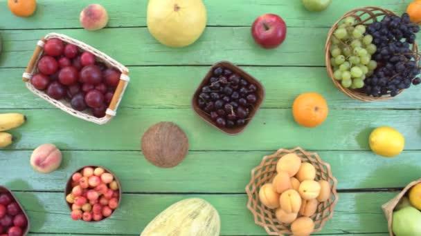 Ovoce na ekologické pozadí zelené. Pohled shora. Různé druhy ovoce jsou umístěny na pozadí zelené dřevěné eco. Některé plody jsou v dřevěných košů. Zde jsou: hrozny, pomeranče, švestky, kiwi, hrušky, kokos, banány, meloun, švestky, granátového jablka, broskve.