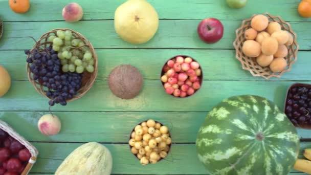 Ovoce na ekologické pozadí zelené. Pohled shora. Různé druhy ovoce jsou umístěny na pozadí zelené dřevěné eco. Zde jsou: meloun, banány, hrušky, kokos, broskve, švestky, kiwi, meloun, švestky, granátové jablko