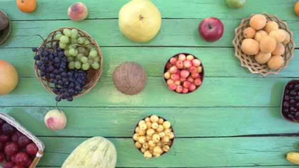 Ovoce na ekologické pozadí zelené. Pohled shora. Různé druhy ovoce jsou umístěny na pozadí zelené dřevěné eco. Ruce položte meloun na stůl eco. Zde jsou: meloun, třešně, švestky, kiwi, banány, hrušky, kokos, broskve.