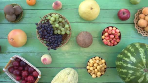 Ovoce na ekologické pozadí zelené. Pohled shora. Různé druhy ovoce jsou umístěny na pozadí zelené dřevěné eco. Dámské ruce si meloun z eco tabulky. Zde jsou: meloun, třešně, švestky, kiwi, banány, hrušky, kokos, broskve
