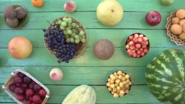 Ovoce na ekologické pozadí zelené. Pohled shora. Různé druhy ovoce jsou umístěny na pozadí zelené dřevěné eco. Ruce si meloun z eco tabulky. Zde jsou: meloun, třešně, banány, hrušky, kokos, švestky, kiwi, broskve
