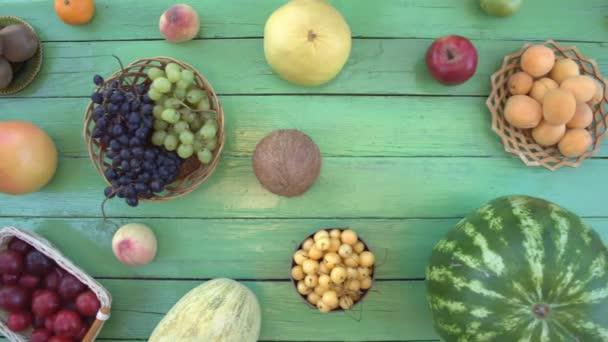 Ovoce na ekologické pozadí zelené. Pohled shora. Různé druhy ovoce jsou umístěny na pozadí zelené dřevěné eco. Dámské ruce položte třešně na stůl eco. Zde jsou: třešně, banány, hrušky, švestky, broskve, jablka, pomelo, grapefruit.