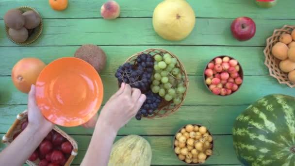 Ovoce na ekologické pozadí zelené. Pohled shora. Různé druhy ovoce jsou umístěny na pozadí zelené dřevěné eco. Dámské ruce si hrozny a nektarinky eco tabulky. Zde jsou: třešně, banány, hrušky, švestky, meloun, jablka, pomelo, grapefruit