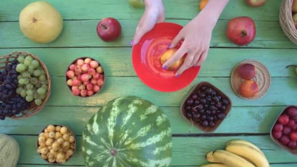 Ovoce na ekologické pozadí zelené. Pohled shora. Různé druhy ovoce jsou umístěny na pozadí zelené dřevěné eco. Dámské ruce si hrozny a nektarinky eco tabulky. Zde jsou: třešně, banány, hrušky, švestky, meloun, jablka, pomelo, grapefruit.