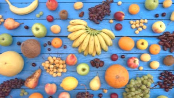 Gyümölcsök ökológiai kék háttéren. Felülnézet. Különböző gyümölcsök háttér színes fából készült eco találhatók. Íme: nektarin, cseresznye, alma, őszibarack, gránátalma, szőlő, banán, citrom, körte, sárgadinnye, kókusz, szilva.