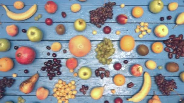 Ovoce na modrém ekologické pozadí. Pohled shora. Různé druhy ovoce jsou umístěny na barevné dřevěné eco pozadí. Zde jsou: hrozny, nektarinky, třešně, jablka, broskve, banány, granátové jablko, citron, hrušky, kokos, švestky. Tabulka mokré eco.