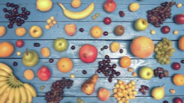 Gyümölcsök ökológiai kék háttéren. Felülnézet. Különböző gyümölcsök háttér színes fából készült eco találhatók. Íme: őszibarack, banán, kókuszdió, szilva, gránátalma, szőlő, nektarin, meggy, alma, citrom, körte. Nedves eco táblázat.