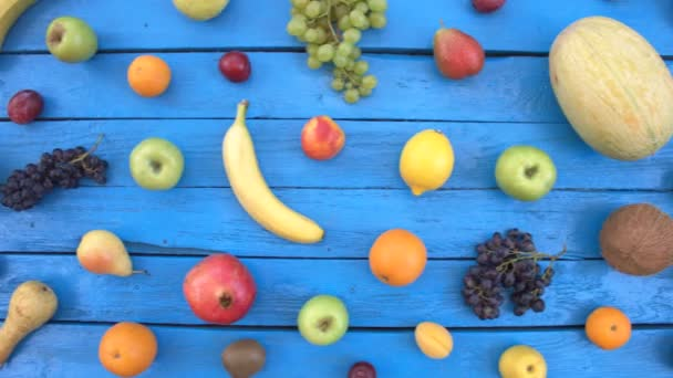 Ovoce na modrém ekologické pozadí. Pohled shora. Různé druhy ovoce jsou umístěny na barevné dřevěné eco pozadí. Zde jsou: jablka, broskve, banány, třešně, nektarinky, granátové jablko, citron, hrušky, meloun, kokos, švestky.