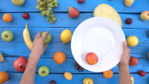 Fruits on blue ecological background. Top view.Various fruits are located on colorful wooden eco background. Mens hands take fruits on plate. Apples, peaches, nectarines, lemon, pears, bananas, cantaloupe, coconut, plums, pomegranate.
