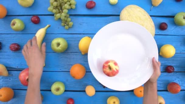 Gyümölcsök ökológiai kék háttéren. Felülnézet. Különböző gyümölcsök háttér színes fából készült eco találhatók. Férfi kezébe veszi gyümölcsök lemez. Alma, őszibarack, nektarin, citrom, körte, banán, sárgadinnye, kókusz, szilva, gránátalma.