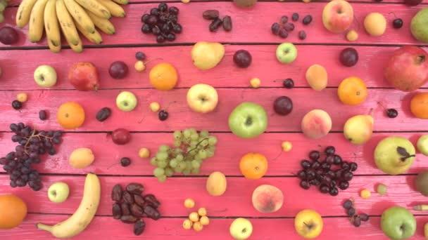 Ovoce na růžové ekologické pozadí. Pohled shora. Různé druhy ovoce jsou umístěny na růžové dřevěné eco pozadí. Zde jsou: třešně, jablka, broskve, banány, nektarinky, citron, hrušky, meloun, kokos, švestky