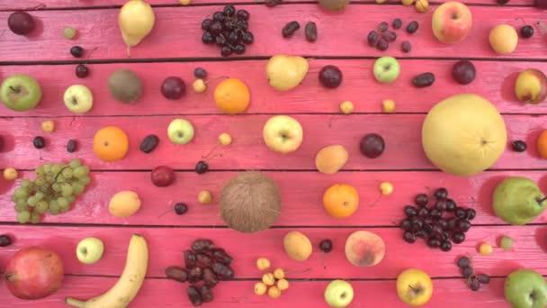 Ovoce na růžové ekologické pozadí. Pohled shora. Různé druhy ovoce jsou umístěny na růžové dřevěné eco pozadí. Ruce si pomelo od stolu. Zde jsou: pomelo, třešně, jablka, broskve, datum ovoce, banány, nektarinky, citron, hrušky, kokos, švestky