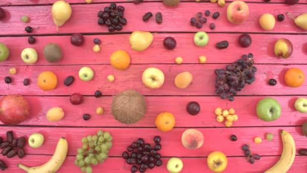 Gyümölcs rózsaszín ökológiai háttér. Felülnézet. Különböző gyümölcsök találhatók rózsaszín fa eco háttér. Férfi kezét szőlő táblából veszi. Íme: szőlő, cseresznye és a meggy, nektarin, alma, őszibarack, dátum gyümölcs, banán, citrom, körte, kókusz, szilva.
