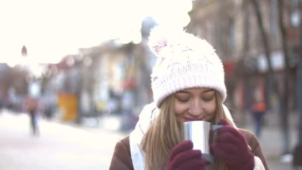 A lány az utcán. Lány forró italt iszik. Ő néz ki mesés mosolya. Szemmel néz legyőz, fúj a szél az arcába. Téli.