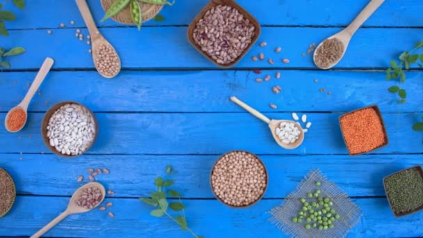 Legumes on wooden ecological background.Beans are located in unusual form on blue wooden table. Hands put plate with green peas on table. Bean cultures in wooden bowls. peas lie on napkin. Camera moves from right to left.