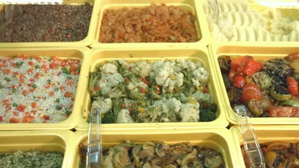 K jídlům v supermarketu. Různé doplnky jsou umístěny na vitríny: Dušená zelenina, dušenou rýží, grilovaná zelenina, Evropská pilaf, houby, zelí, pohanka, bramborová kaše.
