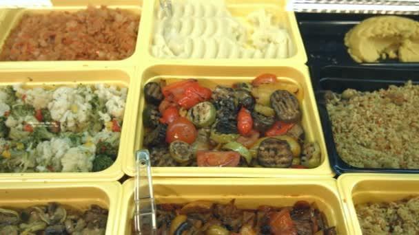 K jídlům v supermarketu. Různé doplnky jsou umístěny na vitríny: Dušená zelenina, dušenou rýží, grilovaná zelenina, Evropská pilaf, houby, zelí, pohanka, brokolice.