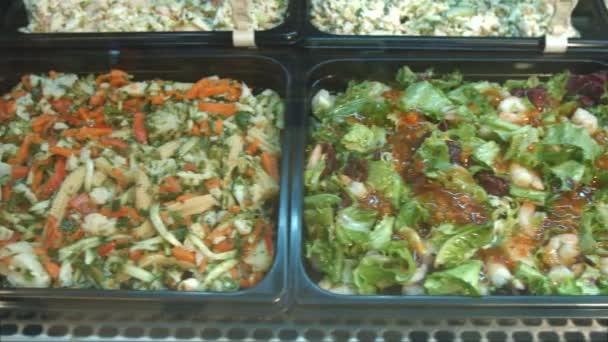 Sada různých salátů. Saláty v supermarketu: krevety a avokádový salát, Řecký salát, salát z mořských plodů, čínský salát, salát ze zelených a zeleniny.