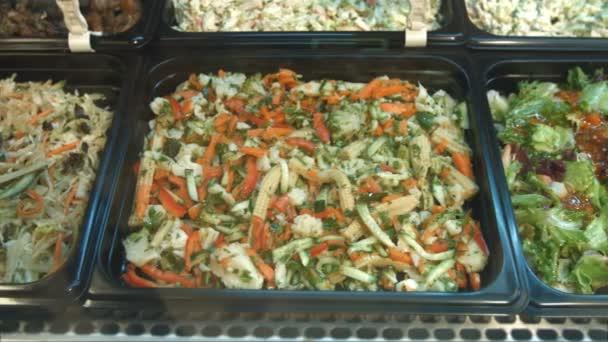 Sada různých salátů. Saláty v supermarketu: čínský salát, krevety a avokádový salát, Řecký salát, salát z mořských plodů, salát ze zelených a zeleniny.