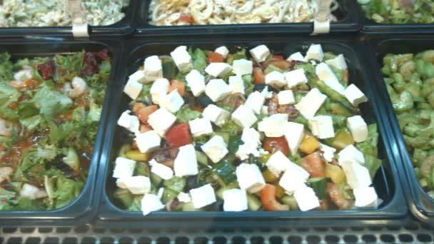 Sada různých salátů. Saláty v supermarketu: salát z mořských plodů, garnátů a avokádový salát, Řecký salát, čínský salát, salát ze zelených a zeleniny.