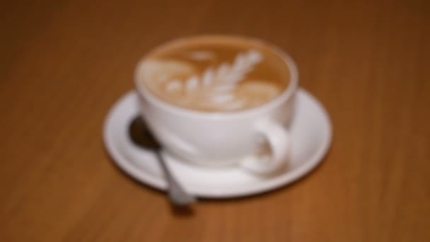 Coffee and foam on cappuccino.Coffee on table in restaurant. Drawing of milk on a cappuccino. Beautiful ornament in the form of a flower. Jewelry work with foam and milk.