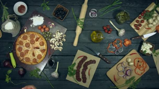 Pizza Pepperoni su sfondo nero ecologico. La ragazza scatta una foto per telefono di pizza ai peperoni. Pizza con ripieno: salame, formaggio diverso. Ci sono anche molti altri prodotti sul tavolo per cucinare e mangiare pizza.