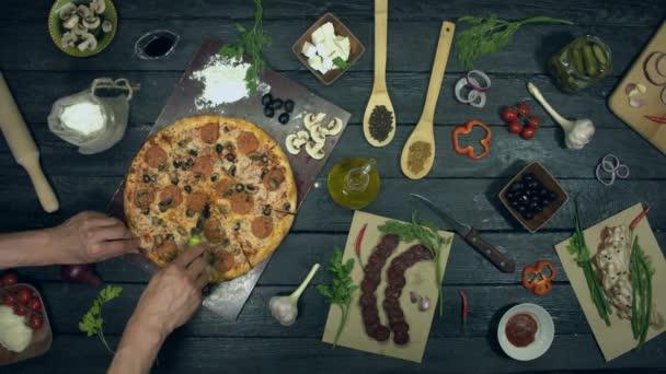 Pizza na ekologickém černém pozadí. Muž si rozdává pizzu a dá ji dívce. Masová Pizza s odlišným plněním: salám, houby, klobása, sýr, olivy. Na stole je také mnoho dalších produktů pro vaření a stravování pizzy.