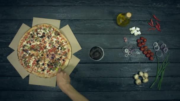 Vegetariánská Pizza na ekologickém černém pozadí. Člověk si na pizzu vezme sklenici piva a kus pizzy. Pizza s různým plněním: rajčata, papriky, houby, různé sýry, olivy. Na stole je mnoho dalších produktů pro konzumní pizzu.