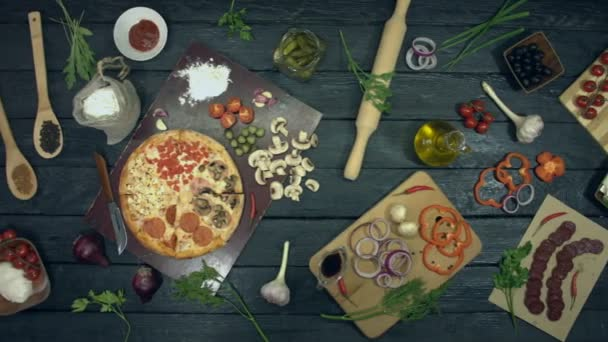 Pizza on ecological black background.Pizza with different filling: ham, salami, mushrooms, tomatoes, different cheese. There are also many other products on table for cooking and eating pizza.